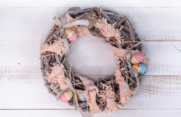 Handmade easter wreath made of twigs and ribbons with cute bird and wooden eggs