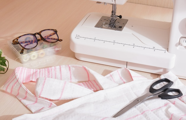 Эко-сумка для покупок ручной работы из хлопчатобумажной ткани, швейная машинка, ножницы, стаканы и катушки с нитками на столе