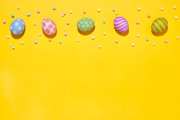 Творческие яйца макета праздника пасхи покрасили handmade краску ed с партией пены ленты на желтой предпосылке. сезонная концепция положения квартиры.