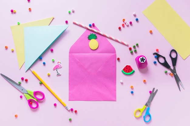 Handmade envelope surrounded with decorative items on pink background