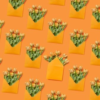 黄色の背景に新鮮なチューリップの束を持つ手作りの封筒。おめでとうポストカード。