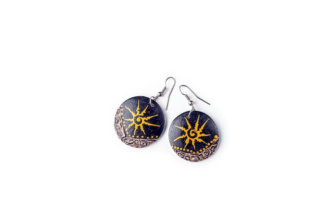 Handmade ethnic wooden earrings with painted pattern on white table. ancient asian-oriental jewelry. copy space, close-upb