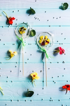 Handmade flat round lollipops with flowers or beads inside on blue wooden surface. pattern of candy, flowers and pastry silver beads