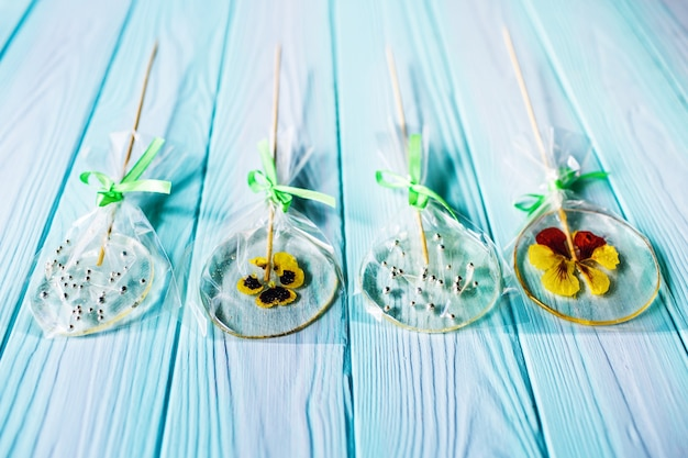 Handmade flat round lollipops with flowers or beads inside on blue wooden surface.