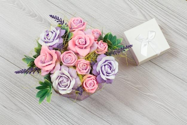 灰色の木の表面に手作りの花とギフトボックス