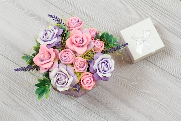 Handmade flowers and a gift box on the gray wooden surface