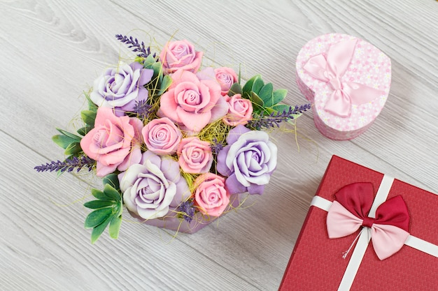 Handmade flowers and gift boxes on the gray wooden surface