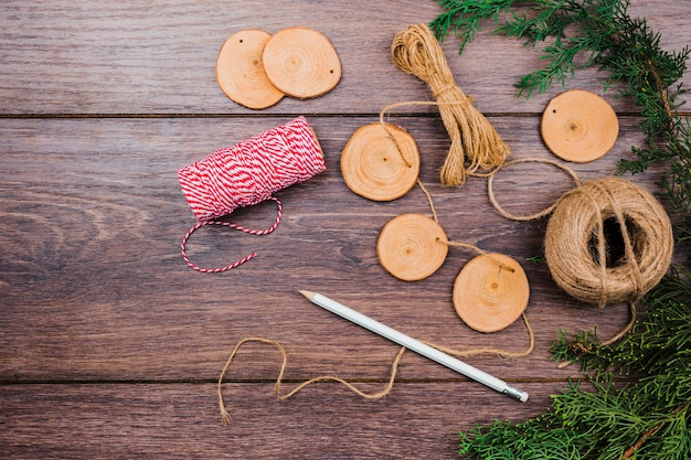 Handmade garland for thread; wooden tree stump slice; pencil and spruce branch on wooden desk