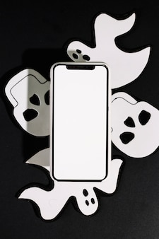 Handmade ghosts and skulls with mobile phone made of paper