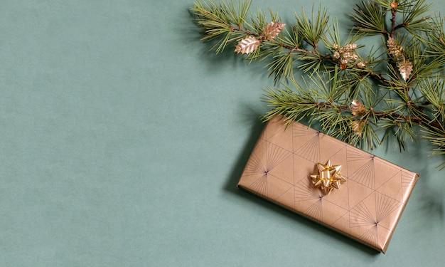 きらめく環境にやさしい紙に包まれた手作りのギフトボックス、輝くつまらないものが付いたクリスマスツリーの枝。