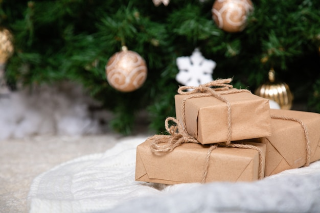 Handmade gift boxes on floor near fir tree