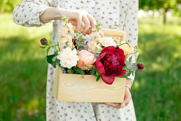Handmade gift made from peach roses, peonies, red roses, packed in a wooden box.