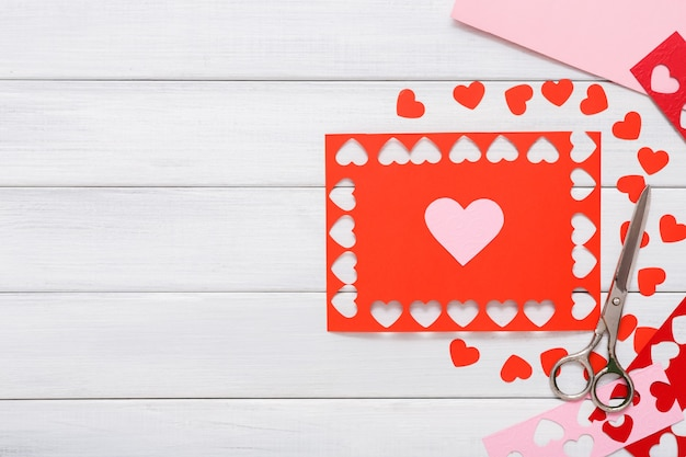 手作りギフト赤いハートの作成、カットアンドペースト、クラフト紙、白い木にdiyツール