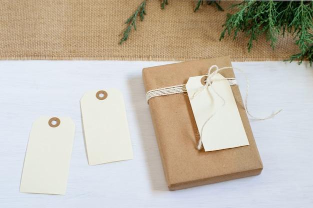 黄麻布の織り目加工のテキスタイルに結ばれた茶色のクラフト紙の結び目で包まれた手作りのギフト
