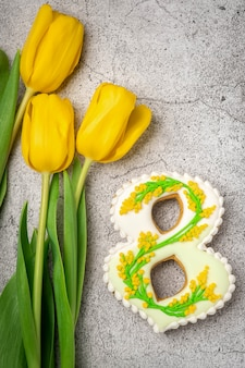 Handmade gingerbread in the form of numbers eight on a concrete gray table and yellow tulips