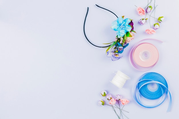 Handmade hairband made with artificial flowers; spool and ribbon on white backdrop