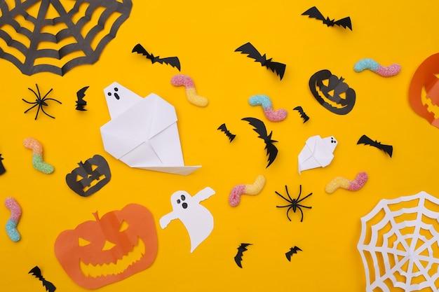 노란색 배경에 수제 할로윈 종이 장식과 거미 벌레. 할로윈 배경입니다. 평면도. 플랫 레이