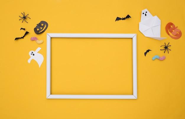 손으로 만든 할로윈 종이 장식, 노란색 배경에 거미 벌레가 있고 텍스트에 흰색 프레임이 있습니다. 공간을 복사합니다. 할로윈 배경입니다.