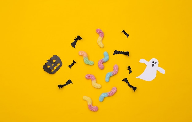 Handmade halloween paper decor and gummy worms on yellow background. halloween background. top view. flat lay