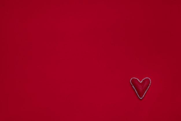 フェルトの表面に手作りのハート。プレスウール、ファブリック、スレッド。 2月14日バレンタインデー