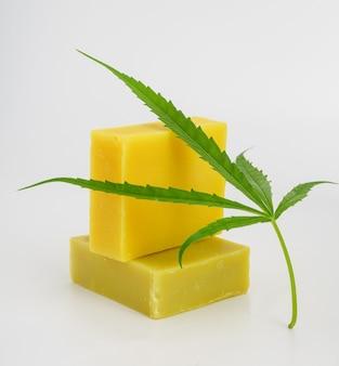 Handmade hemp soap bars and cannabis leaf isolated on white background