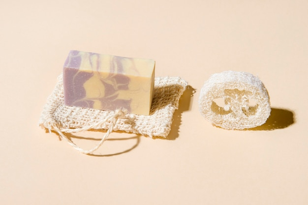 Handmade hemp soap and loofah sponges on a beige background. eco lifestyle concept.