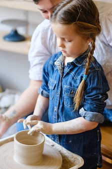 手作りの趣味陶芸コース。ワークショップでのマスタークラス。小さな学生の子供と一緒に回転ホイールで粘土を形成する陶芸家