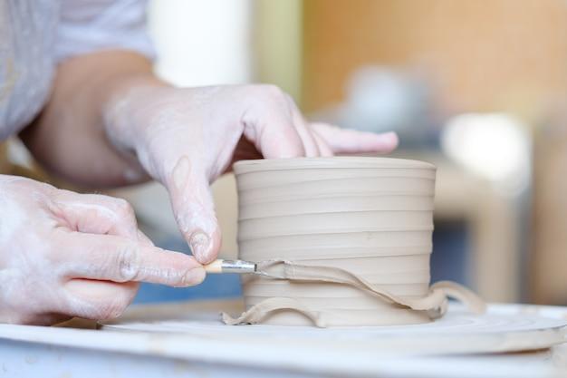 手作りの趣味陶芸コース。ワークショップでのマスタークラス。回転ホイールで粘土を形成する陶芸家