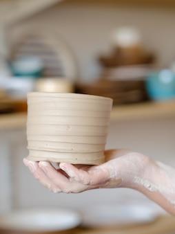 手作りの趣味陶芸コース。ワークショップでのマスタークラス。クラフト粘土の水差しを保持している陶芸家