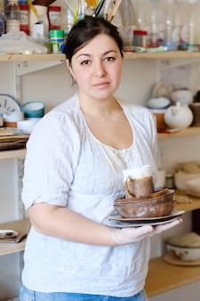 手作りの趣味陶芸コース。ワークショップでのマスタークラス。クラフト粘土食器を保持している陶芸家