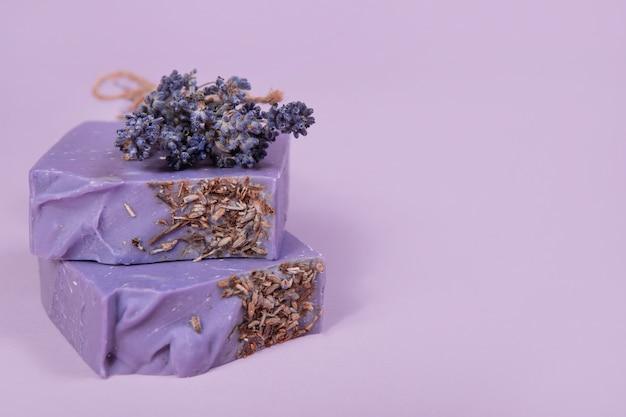 Домашнее мыло ручной работы на сиреневом фоне. аромат лаванды. малый бизнес, органические продукты, натуральные ингредиенты.
