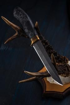ダマスカス鋼で作られた手作りの狩猟用ナイフが角に横たわっています
