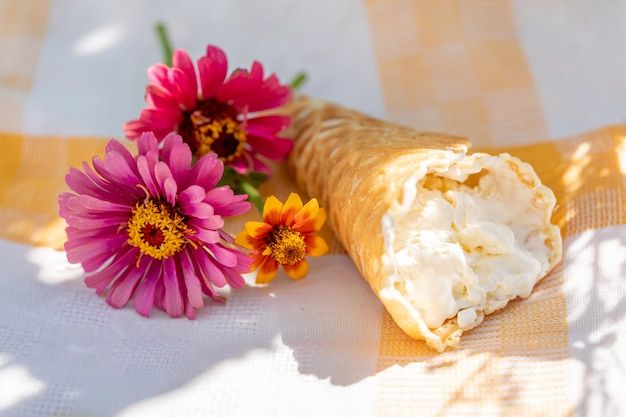 Мороженое ручной работы в вафельном рожке и небольшой букет цветов на льняной салфетке в жаркий летний день