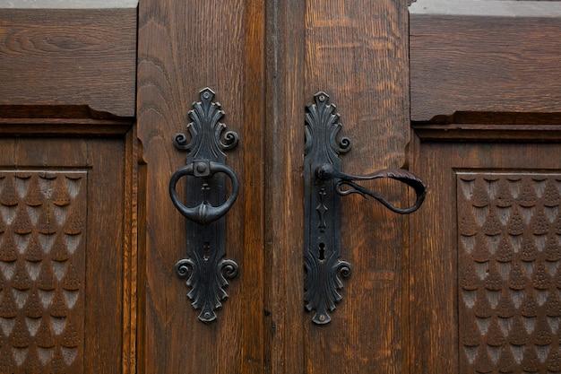 茶色の装飾的な木製のドアの手作りの鉄のドアハンドル。クローズアップショット