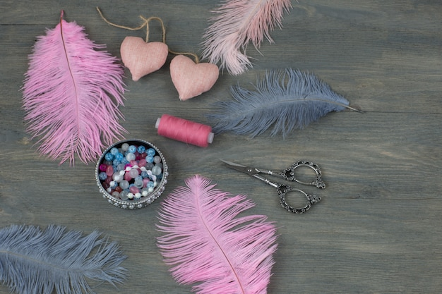 Handmade items on a wooden background: colorful feathers, beads, pearls, scissors, threads
