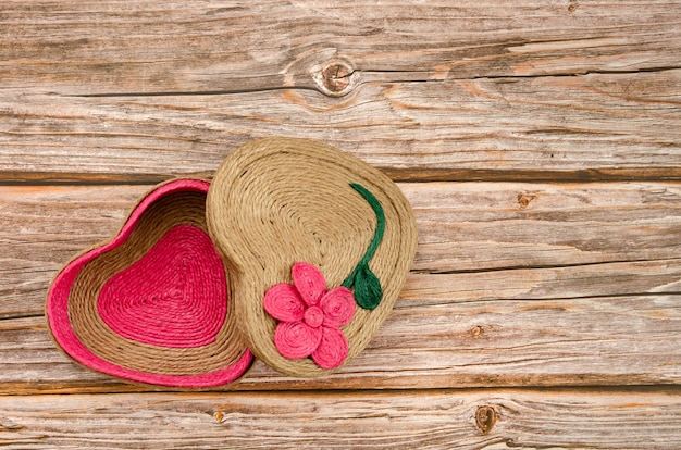 Шкатулка ручной работы в форме сердца на деревянном столе.