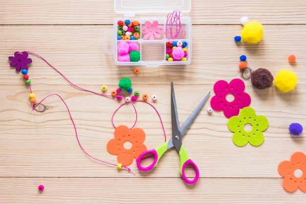 Handmade jewelry made with beads and flower patch on wooden backdrop