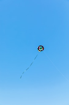 Handmade kite flying with a blue sky