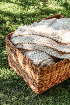 Handmade knitted beige plaid in basket.