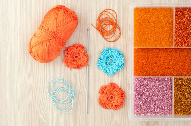 Handmade knitted crochet flowers. box with beads to create hand made jewelry on a wooden table. top view