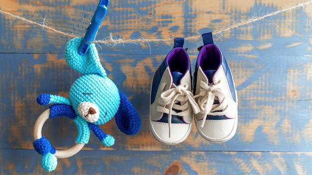 Handmade knitted toy for kids and small shoes pinnet on a yarn. top view