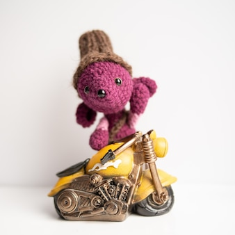 Handmade knitted toy. a rat crocheted with a yellow motorcycle