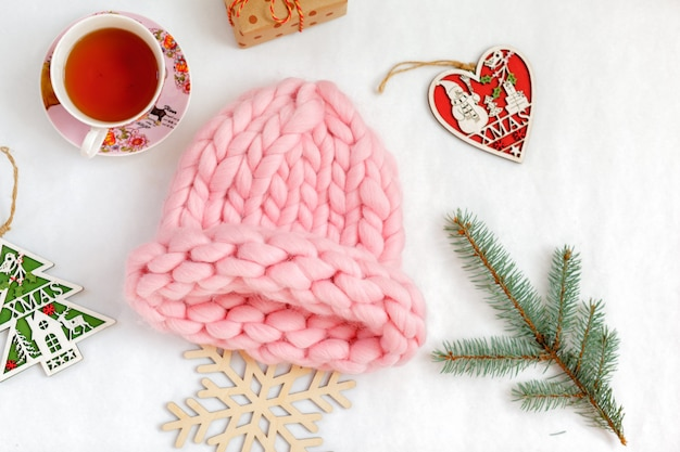 Handmade knitwear composition with warm hat of pastel color
