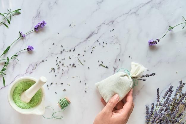 Саше ручной работы из лаванды и домашний сахарный скраб. рука держит льняной мешок с сухими цветами лаванды. вид сверху на белый мрамор.