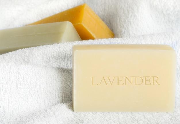 흰색 목욕 수건 배경에 수제 라벤더 비누입니다.