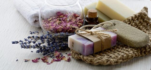 목욕 및 스파 액세서리가 포함된 수제 라벤더 비누. 배너 또는 배경을 위한 아로마 오일이 있는 말린 라벤더와 장미 꽃잎