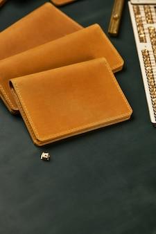 Кожаные аксессуары ручной работы, подобранные в одном цвете, модные, домработница, кошелек, визитница горчично-желтого цвета на зеленом фоне.