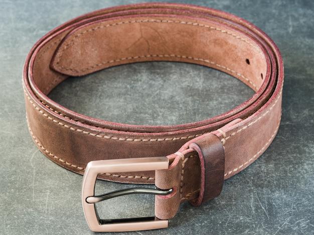 Кожаный ремень ручной работы с бронзовой пряжкой, часть ремня и поверхность красиво размыты, лежит на серой фактурной поверхности.