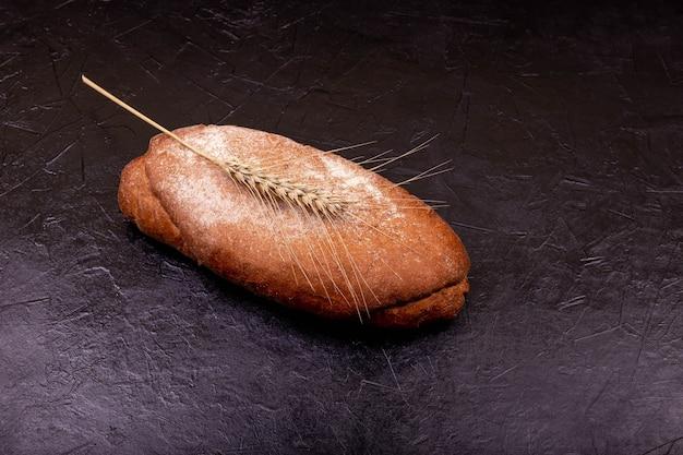 石の黒い表面に手作りのパン。焼きたての自家製パン。