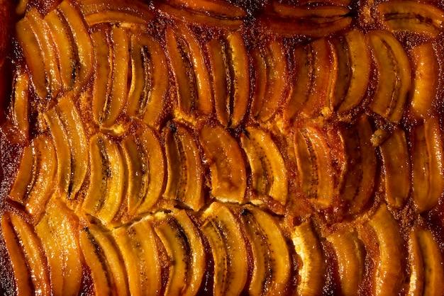 자연광에서 계피를 곁들인 수제 롱 슬라이스 카라멜라이즈 바나나 케이크. 상위 뷰를 닫습니다.